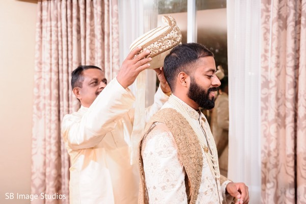 Indian groom being assisted with his groom.