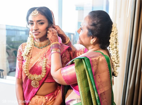 Maharani being assisted with her earrings.