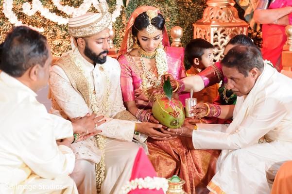 Indian couple in coconut ritual.