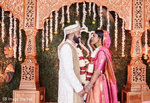 Maharani wearing a pink lengha and his Indian groom.