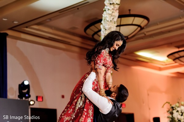 Indian groom lifting his Maharani in red lengha.