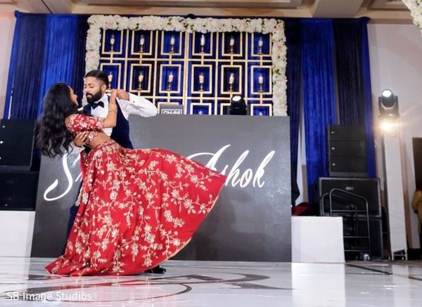 Indian couple in reception wear dancing.