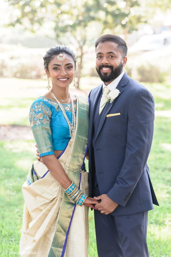 Indian couple posing on their Indian christian wedding outfits.