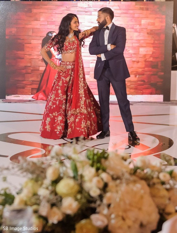 Indian couple posing on reception dance floor.