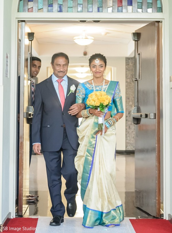 Indian bride walking down the aisle with her father.