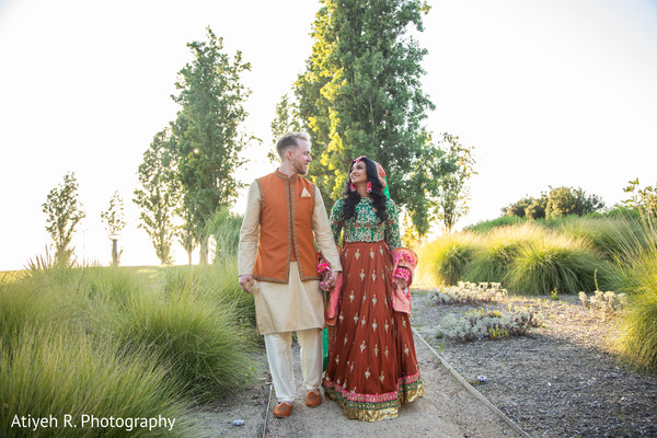 Indian bride and Indian groom walking while holding hands.