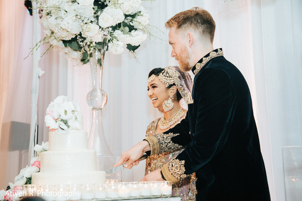 Indian couple cutting a slice of the wedding cake.