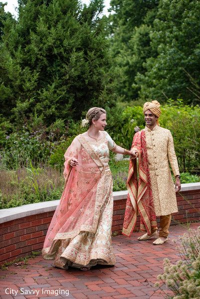 Indian bride and groom walking out of wedding venue.