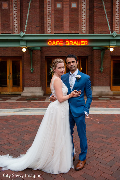 Indian bride and groom on their white and blue reception outfits.
