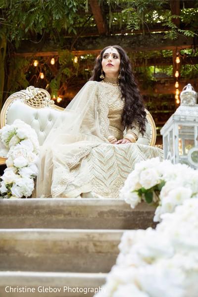Indian bride surrounded by white floral decor arrangements.