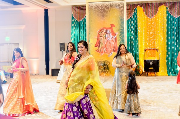Indian bride with bridesmaids on their Sangeet lehengas.