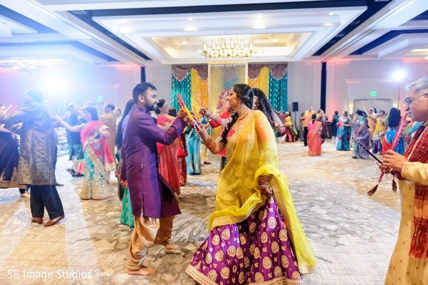 Indian couple dancing at Sangeet with dandiya sticks.