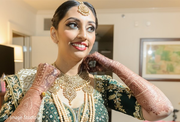 Indian bride putting on her ceremony choker necklace.