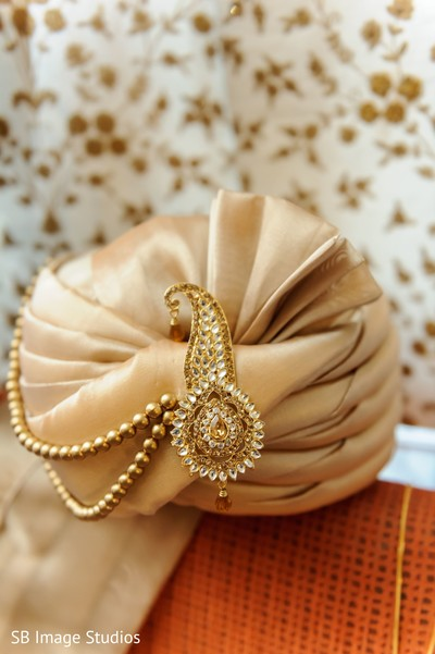 Golden indian groom's turban with jewelry on.