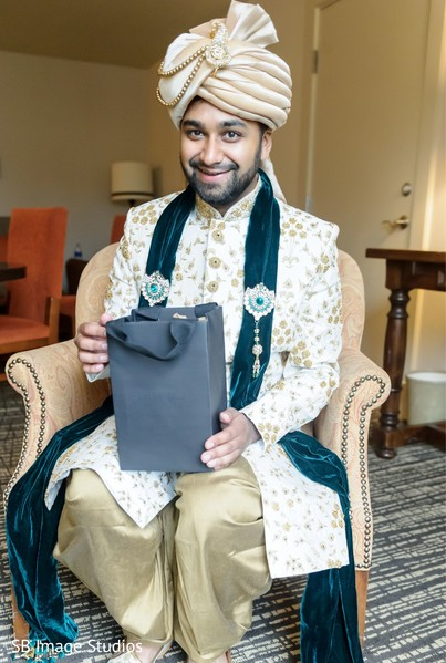 Indian groom on his ceremony outfit holding his present.