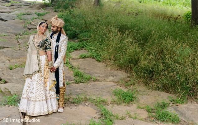 Indian bride and groom holding hands outdoors capture.