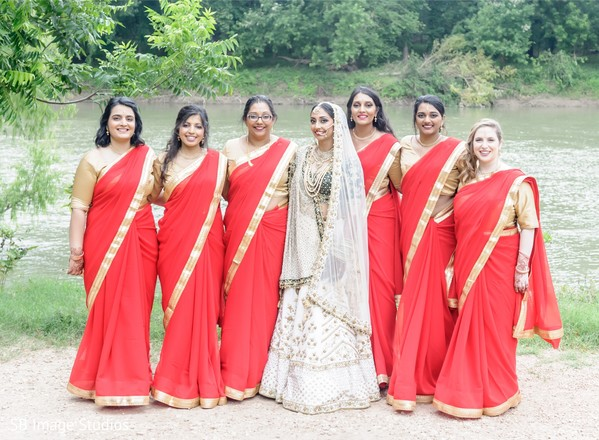 Indian bride posing with bridesmaids on their ceremony outfits.