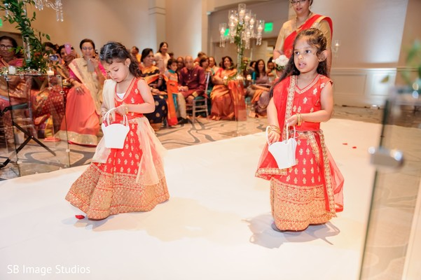 Indian flower girls walking down the aisle on their red lehengas.