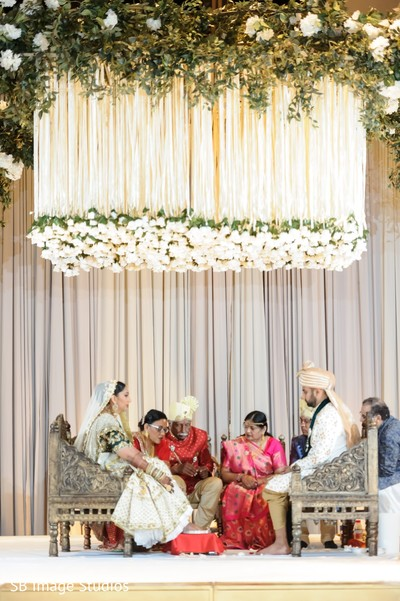 Indian couple seating under the mandap hanging flowers.