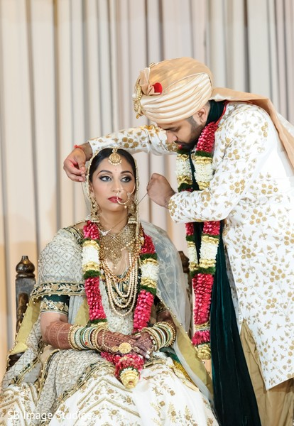 Indian groom puts the chain to bride ritual.