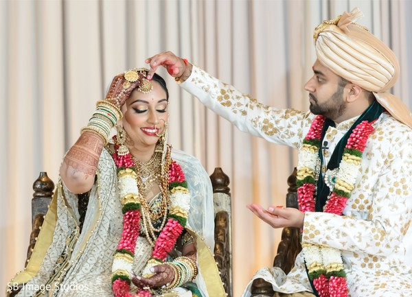 Indian groom putting the red mark on maharani's forehead.