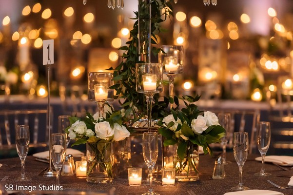 Indian wedding table white roses and candles decorations.