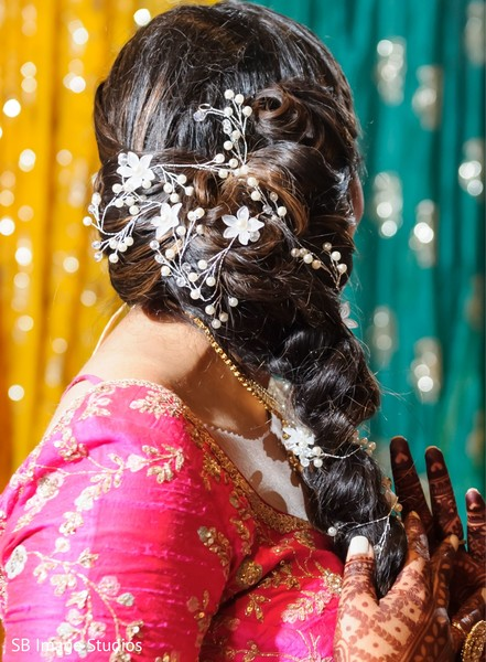 Indian bride's Sangeet hairstyle with flowers decorations.