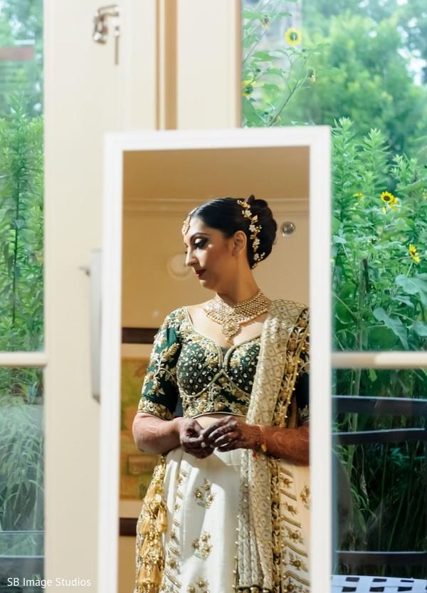 Maharani's mirrored image with her green, golden and white lehenga.