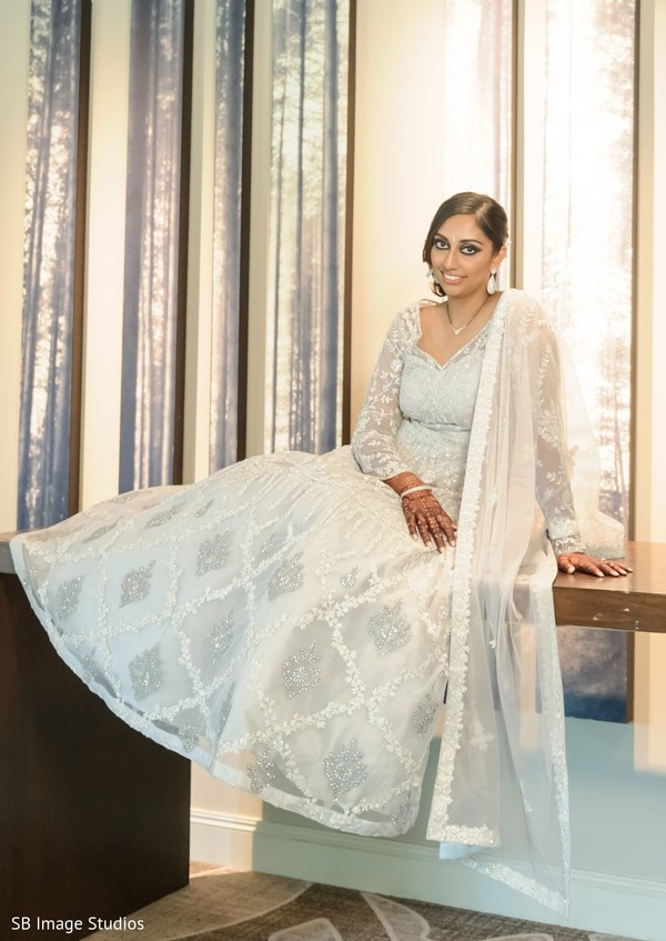 Indian bride posing on her white reception gown.
