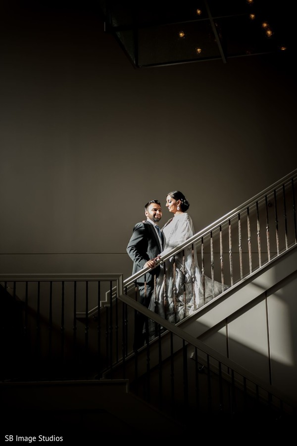 Indian couple posing on the stairs for reception photo session.