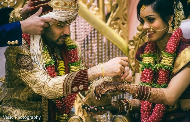 Indian groom tying the knot around Maharani's wrist