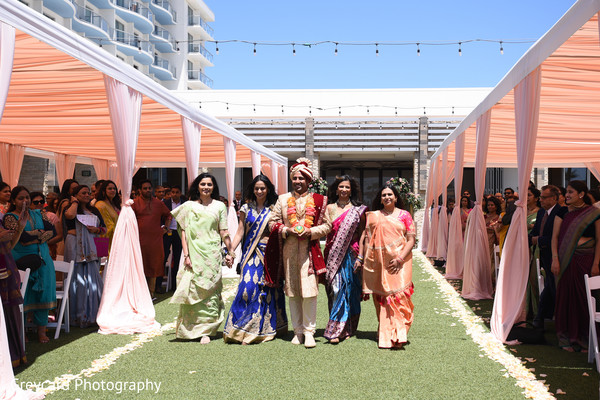 Indian groom being escorted by indian relatives.