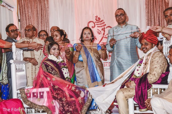 Indian bride and groom with their families during the ceremony.