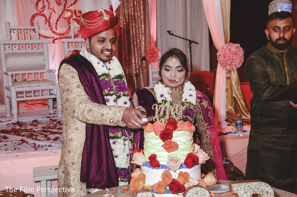 Indian groom and bride cutting the cake during the reception.