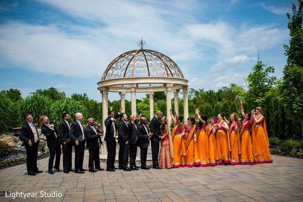 Indian bride and groom outdoors posing with bridesmaids and groomsmen.
