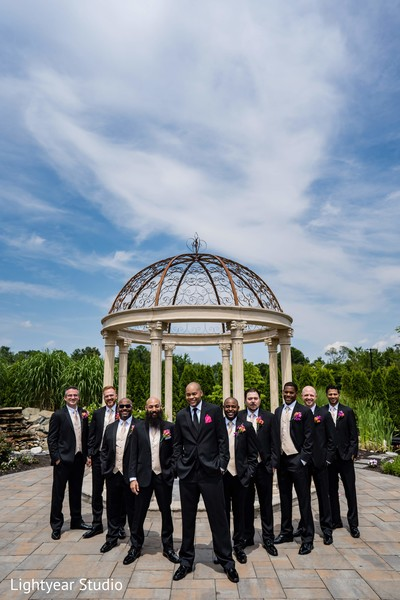 Indian groom with groomsmen outdoors photo session.