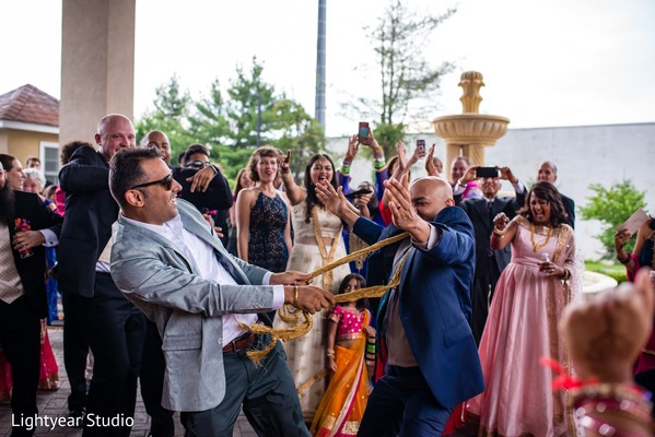 Indian groom running in circles with groomsmen.