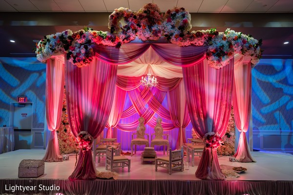 Indian wedding mandap pink lights, flowers and draping decor.