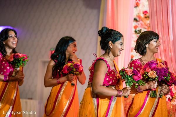 Joyful Indian bridesmaids holding their wedding bouquet.