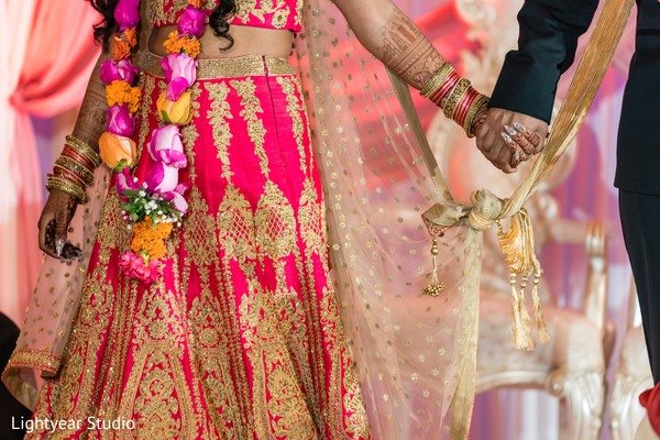Indian bride and groom holding hands during the knot ritual.