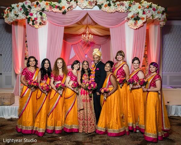 Indian couple and bridesmaids posing at ceremony mandap.