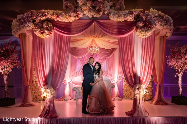 Indian couple posing at pink and white reception  mandap.