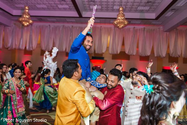 Indian groom up in Indian relatives shoulders
