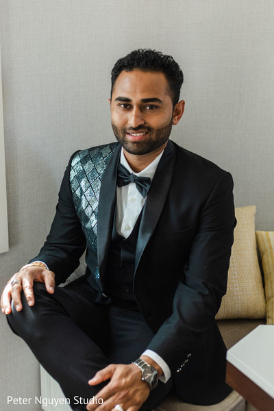 Indian groom wearing a tuxedo posing for picture.