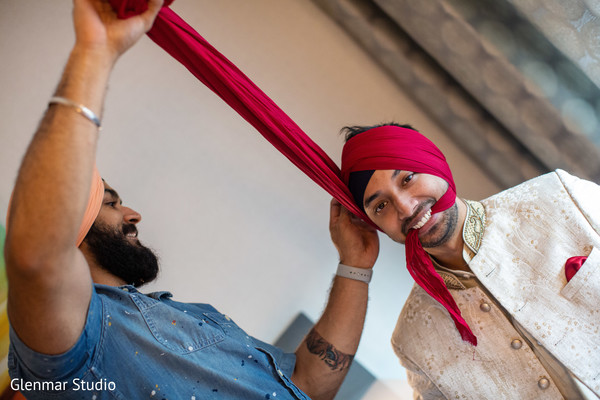 Indian groom being assisted by special guest prior to the ceremony.