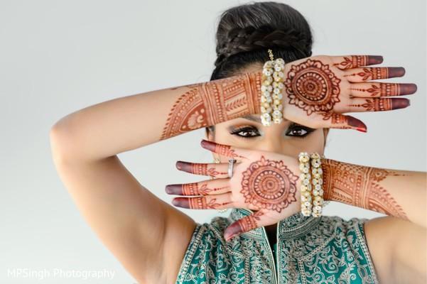 Indian bride showing her henna art with her golden chooras.
