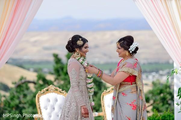 Indian mother putting jaimala to Indian bride.