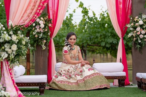 Indian bride posing with her lehenga at mandap .