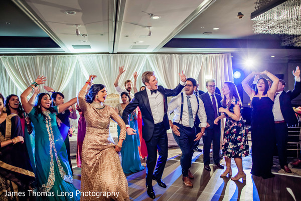 Indian couple dancing with bridesmaids and groomsmen.
