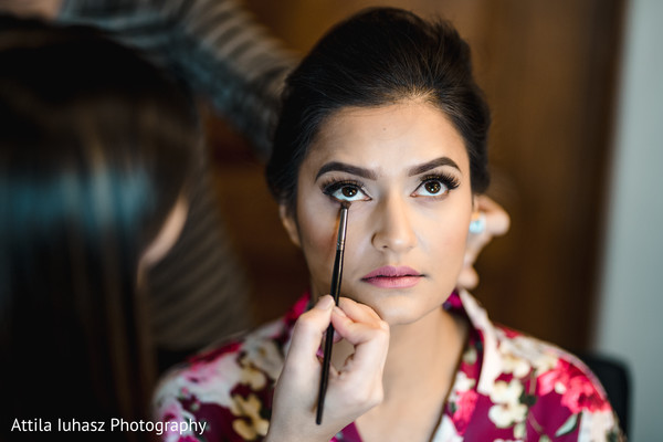 Indian bride getting ready with her make up.